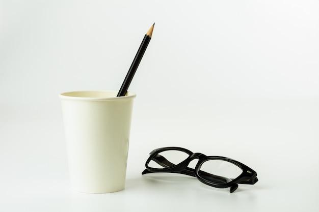 Crayon dans une tasse à café en papier et lunettes de vue sur fond blanc.