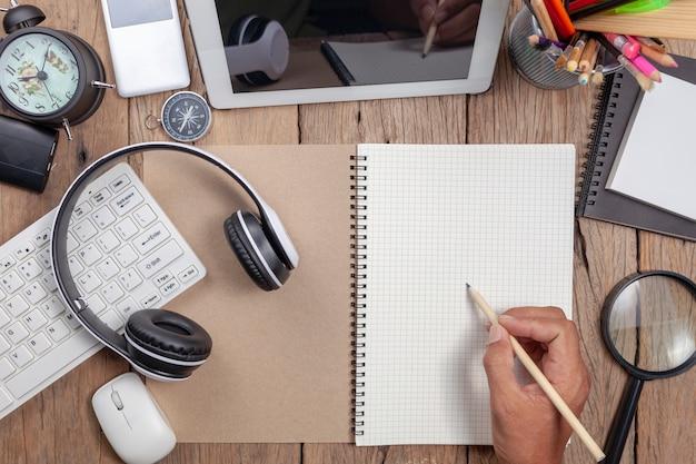 Crayon d'écriture main homme d'affaires sur la note de papier blanc et les objets métier