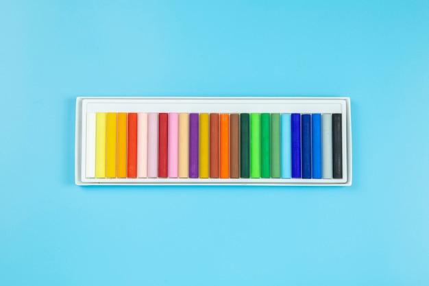 Crayon sur fond bleu style plat à pastel