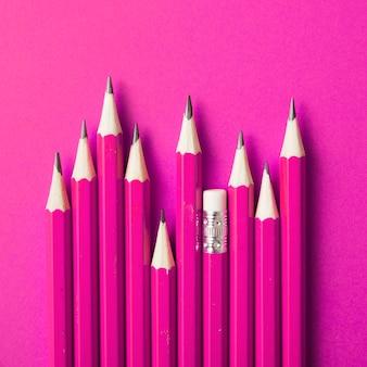 Crayon avec gomme se démarquant des autres crayons pointus sur fond rose