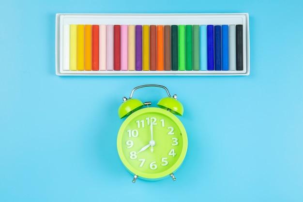 Crayon et horloge verte sur fond bleu style pastel flatlay topview.