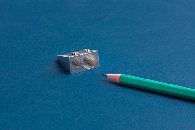 Crayon isolé avec taille-crayon sur fond bleu