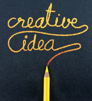 Crayon jaune écrire le mot idée créative sur papier craft noir
