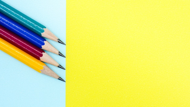 Crayon jaune, rouge, bleu et vert sur papier bleu et jaune - fond