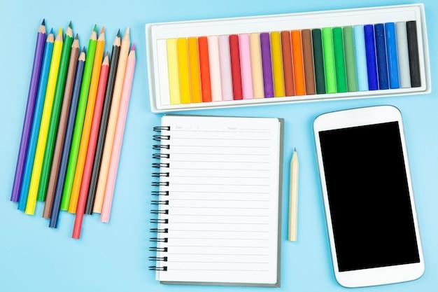 Crayon et livre téléphone portable topview flatlay sur fond bleu style pastel.
