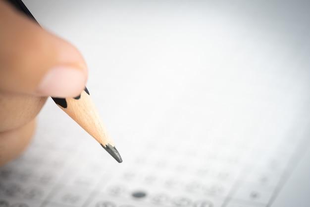 Crayon sur la main qui écrit la réponse du test de l'examen sur le papier de réponse