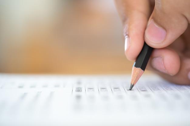 Crayon sur la main qui écrit la réponse de l'examen de la question