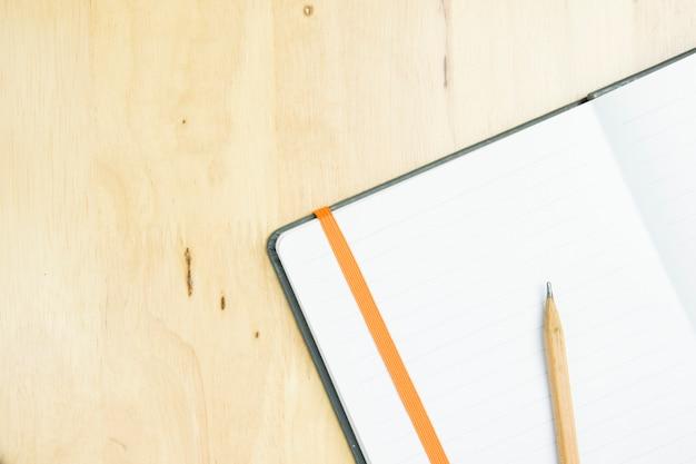 Crayon marron avec carnet de notes sur l'espace de travail en bois. vue de dessus, concept plat laïque.