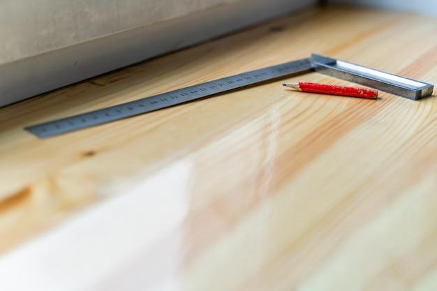Crayon de menuisier rouge et outil à angle droit sur un sol stratifié après des travaux de rénovation ou de reconstruction - mise au point sélective
