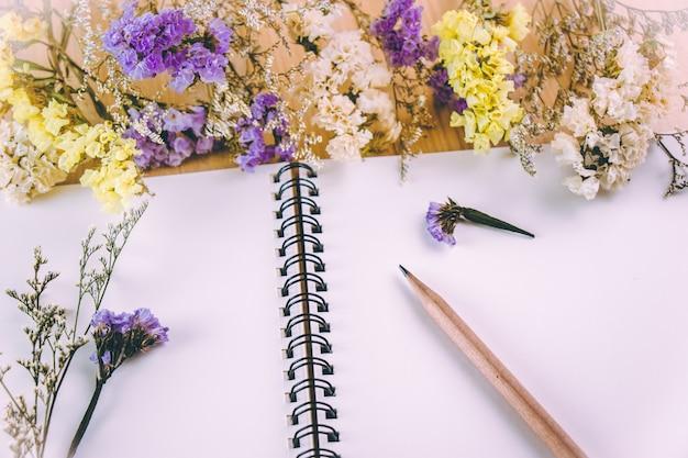 Crayon mettre sur cahier vierge près de bouquet de fleurs, sur une table en bois