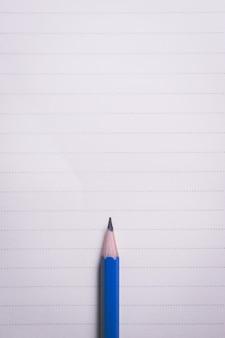 Crayon minimal sur fond de lignes de cahier avec copie vue de dessus.