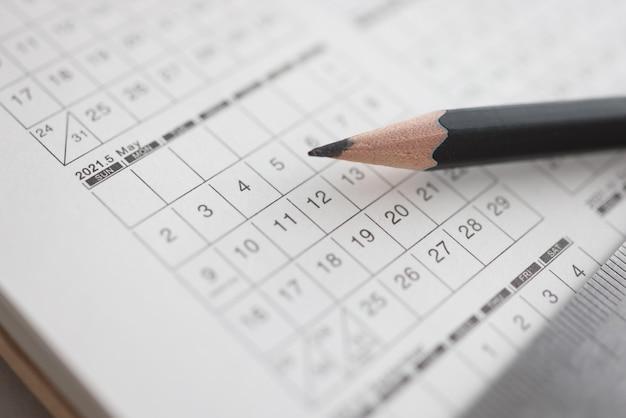 Crayon noir pointu allongé sur le calendrier agrandi