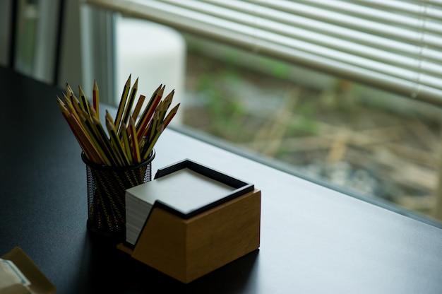 Crayon et note placés sur le bureau. placé par la fenêtre