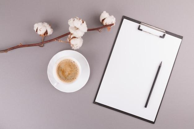 Crayon et papier sur le presse-papiers près de la branche et de la tasse