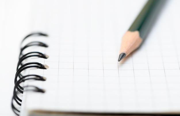 Le crayon de plomb est sur la page vierge du cahier