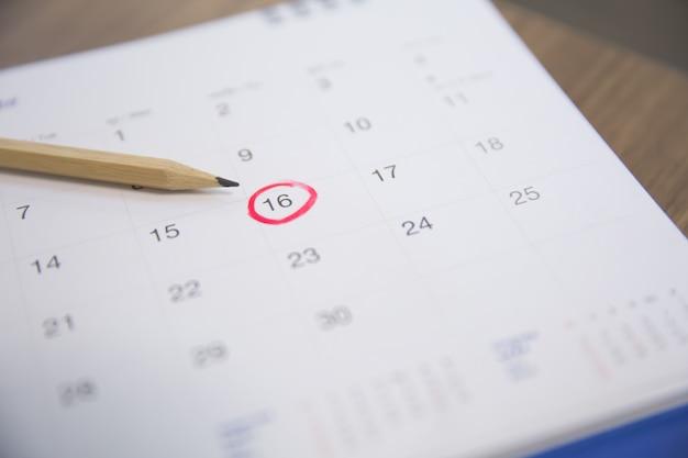 Le crayon pointe vers le chiffre 16 du calendrier.