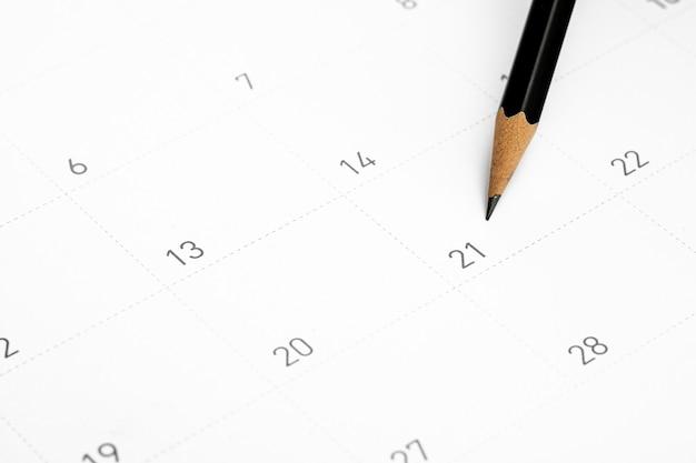 Le crayon pointe vers le vingt et un dans le calendrier