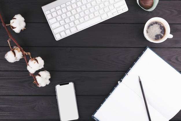 Crayon près d'un cahier, d'une tasse, d'un smartphone, d'une brindille et d'un clavier