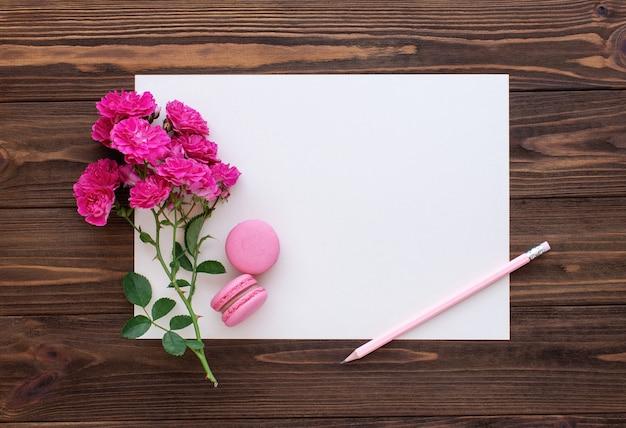 Crayon de roses rouges et carte papier vierge sur fond de bois