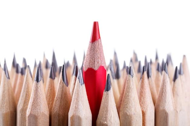 Un crayon rouge aiguisé parmi beaucoup d'autres