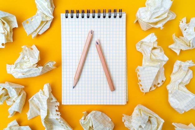 Crayon rouge et cahier sur fond jaune. des feuilles de papier froissées.