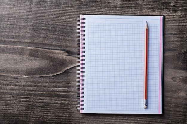 Crayon rouge et cahier vérifié sur le concept d'éducation de planche de bois de pin