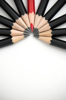Crayon rouge se démarquant de la foule d'abondants camarades noirs identiques sur une table blanche.