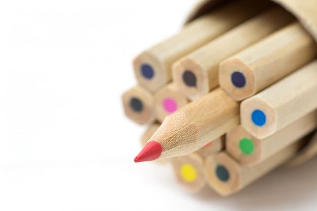 Crayon rouge se démarquant de la foule sur la table blanche.