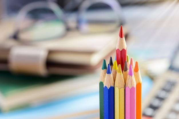 Crayon rouge se démarquant d'un tas de crayons de couleur