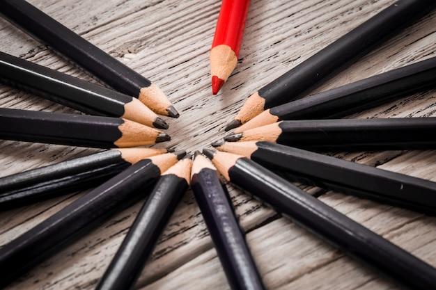 Le crayon rouge se démarque de la foule des noirs sur un fond blanc en bois.