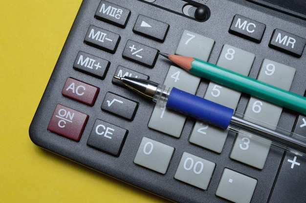 Crayon et stylo calculatrice sur fond jaune. fermer.