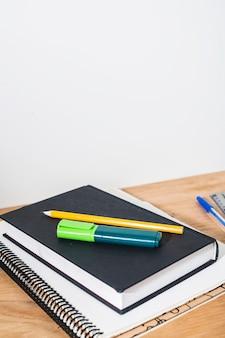 Crayon et surligneur sur le livre et le bloc-notes