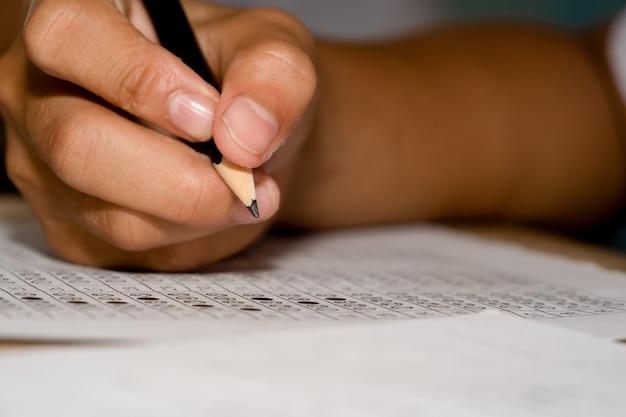 Crayon tenant une main pour écrire la réponse à une question sur du papier à choix multiples
