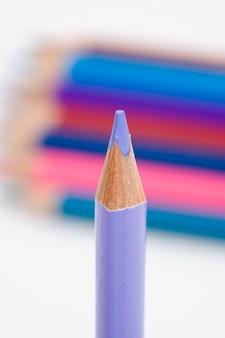 Un crayon violet sur fond de plusieurs couleurs