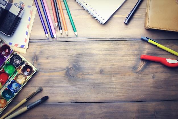 Crayons, aquarelle, papier, pinceau et appareil photo sur table en bois