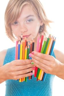 Crayons arc-en-ciel de couleur et mains d'adolescent aux ongles multicolores