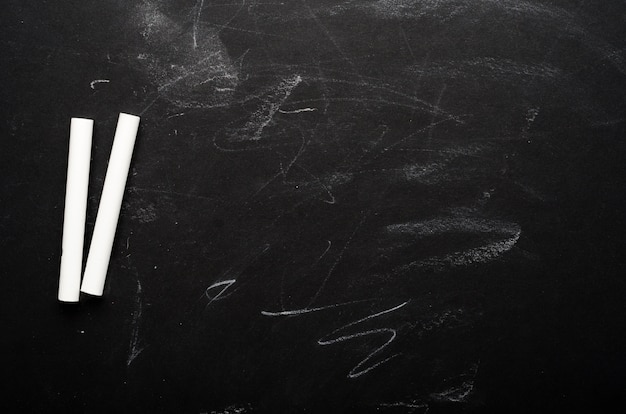 Crayons blancs sur un tableau noir peint. conseil scolaire, contexte conceptuel. copiez l'espace, vue de dessus, pose à plat.