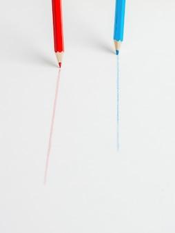 Crayons bleus et rouges dessinant des lignes parallèles sur une surface blanche. le concept de coopération.