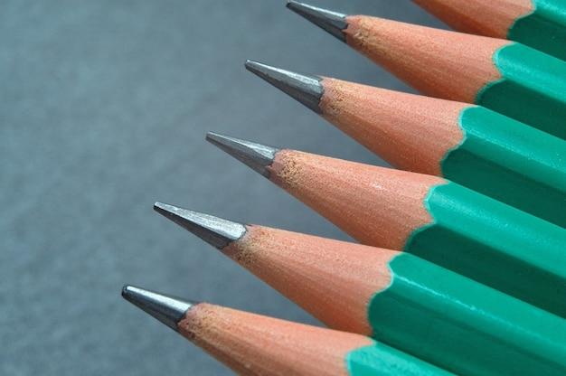 Crayons en bois aiguisés verts avec mine noire sur fond texturé foncé. fermer.