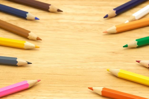 Des crayons de bois colorés entourent un cercle sur un fond de bois.