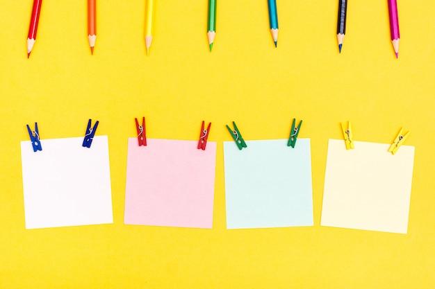 Crayons en bois colorés, épingles et feuilles pour écrire sur un fond jaune