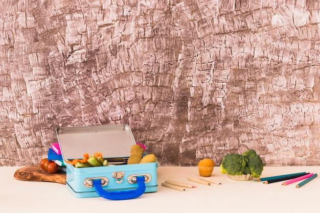 Crayons et boîte à lunch près de mur texturé
