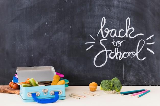Crayons et boîte à lunch près de tableau noir