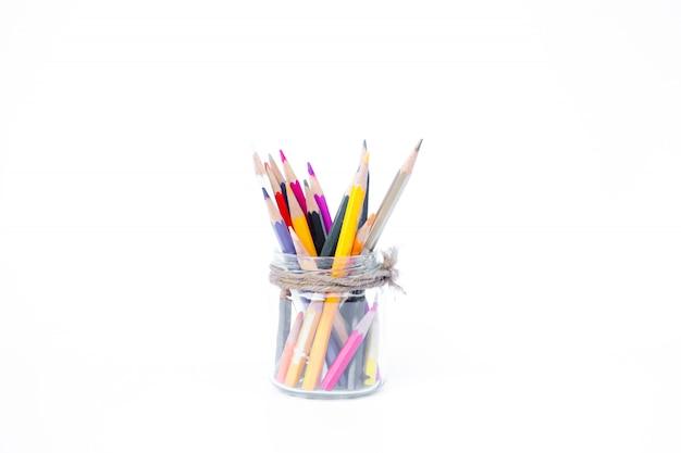 Crayons en bouteilles de verre sur fond blanc
