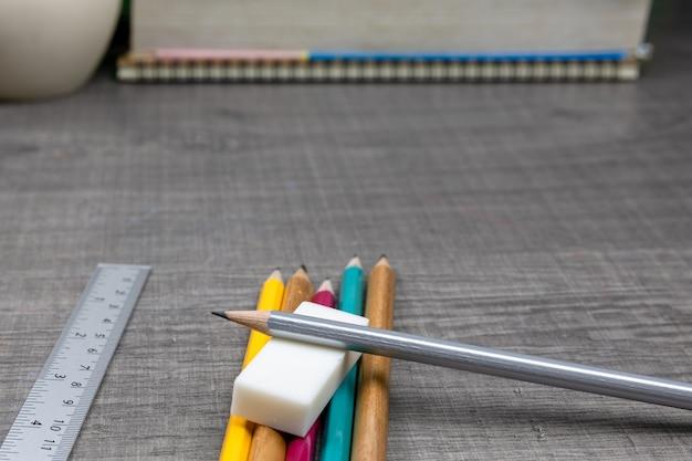 Crayons, cahiers, gommes, règles, livres sur la table le concept à l'école