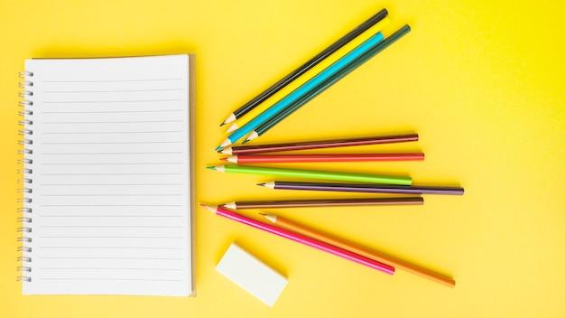 Crayons et caoutchouc près de carnet