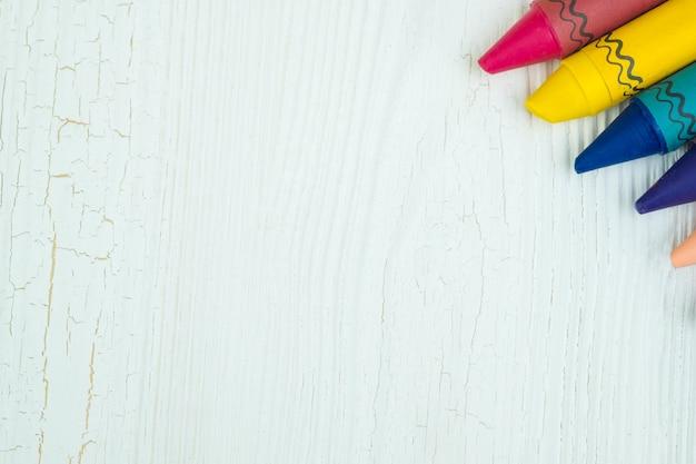 Crayons de cire colorés sur une table en bois blanc