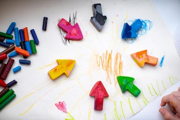Crayons de cire faits maison à partir de l'épave de vieux crayons en les faisant fondre au four à haute température sous forme de silicone. crayons de couleur sous la forme de flèches se trouvent sur le papier, enfant de la main