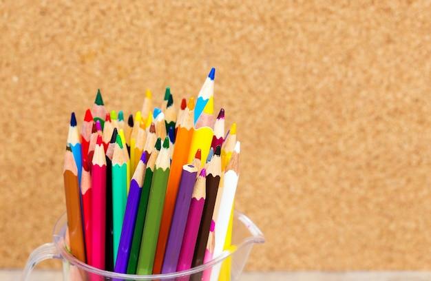 Crayons colol dans une tasse transparente sur une table en bois