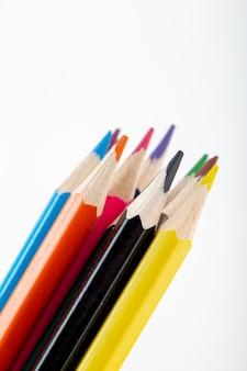 Crayons colorés alignés vue rapprochée pour le dessin et la peinture sur mur blanc